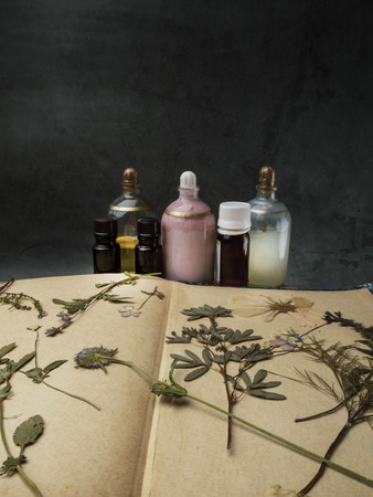 Aroma essential oil. Cosmetic Bottle among dried flowers, medicinal herbs variety. Natural cosmetic and skincare, herbal miscellany, concrete background