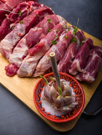 fresh pork with ingredients for cooking on dark concrete background Фото со стока