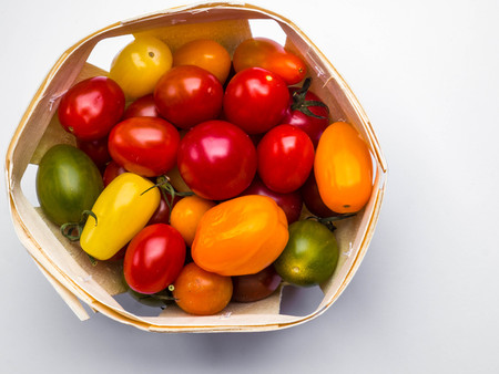 Fresh colorful cherry tomatoes on white background in wooden basket, raw food and vegetable concept