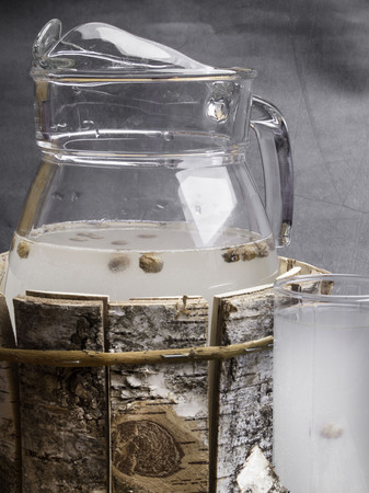 Spring useful vitamin drink. Birch natural juice detox in a glass, jug on concrete background.