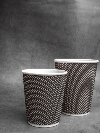 2 sizes of Plastic and Paper coffee cup on grey concrete Table 版權商用圖片