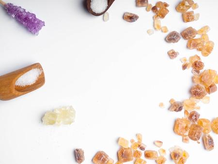 Cube sugar, raw sugar , crystalline sugar and granulation sugar in white background, wooden spoon, copy space