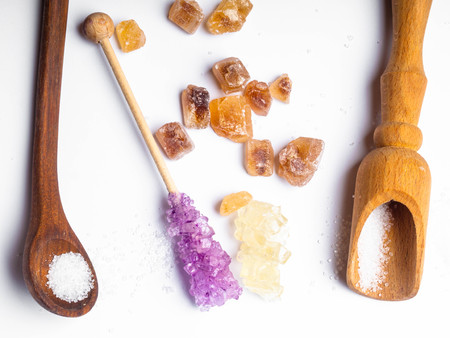 Various types of sugar, brown sugar and white, colored, copy space, on wooden spoons Imagens