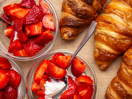 Breakfast with fresh croissants, strawberry in glass bowls background, top view