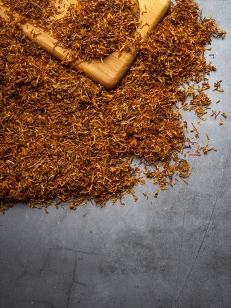 Dry tobacco leaves. High quality tobacco on wooden board close up, background