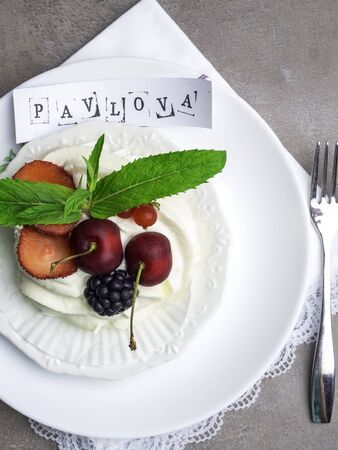 Pavlova meringue cake with fresh berries on white plate with inscription and silver fork