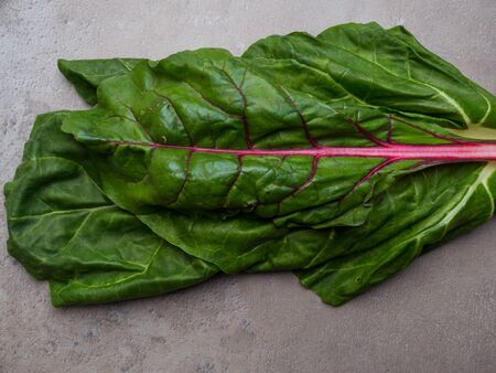 Set of fresh green chard leaves or mangold salad leaves, rich in cellulose and lilac acid on concrete background. Stock Photo