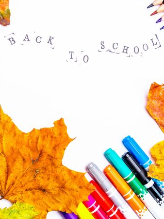 white paper with the inscription back to school with markers, pencils isolated, black stamped text letters