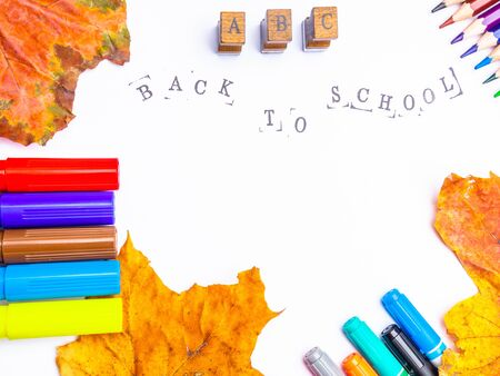 white paper with the inscription back to school with markers, pencils isolated, with black stamped letters Stock Photo