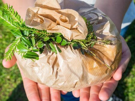 Hands turn paper bag with green leaf and christmas tree branch on it, outdoor