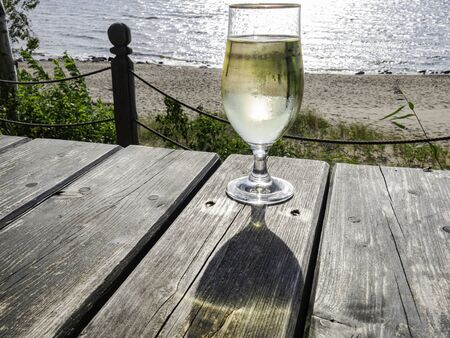Glass of cider on the table against the beach.