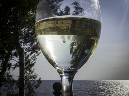Close up of white wine glass with beautiful sea view, toned, relaxation concept Imagens