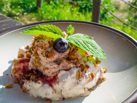 Whipped cream with berry and oatmeal, delicious dessert on white plate Фото со стока - 128281446