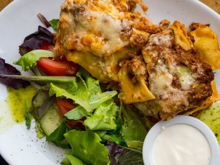 Tomato and beef lasagne with cheese layered between sheets of traditional Italian pasta served on a white plate on a restaurant or bar. Italian food