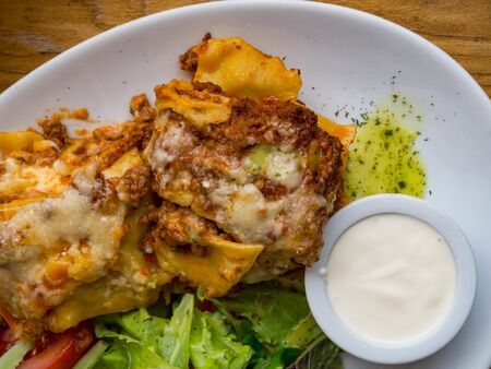 Classic Lasagne - Fast Food, tomato and beef lasagne with cheese layered between sheets of traditional Italian pasta served on a white plate on a restaurant or bar