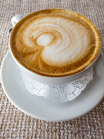 Hot cappuccino with froth and pattern on ackcloth background, a side view