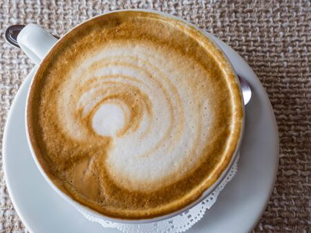 coffee cappuccino or latte in white elegant cup with saucer, on rustic sackcloth a background. Morning hot beverage. Coffee lifestyle. 写真素材