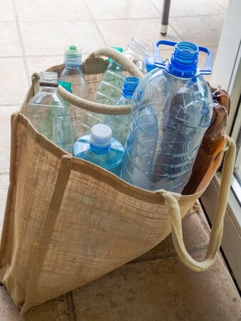 Plastic bottle in burlap bag. Reusable recycling daily use items alternative to disposable. Ecological lifestyle and zero waste concept. free plastic concept, save nature