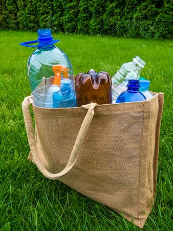 Eco friendly bag for shopping - linen, burlap, mesh bag and colorful plastic bottles. Zero waste background