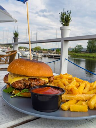 delicious beef burgers with salad trimmings, cheeseburger on a wooden board outdoor with beautiful view Stockfoto