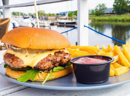 tasty burger with french fries and ketchup outdoor in wooden table in yacht club restaurant close up