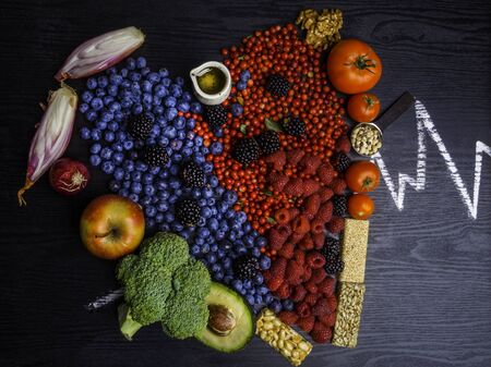Healthy eating and heart health concept with a heart shaped with blueberries, raspberries, blackberries, cranberries. Nuts, oil, salmon, apple, tomato, full of vitamins and antioxidants that can prevent coronary heart disease