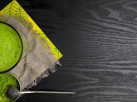 cup with matcha tea latte on black wooden background, detox and antioxidant drink concept