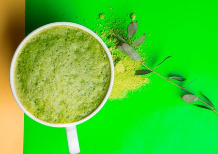 Green matcha tea latte drink and powder on green background. Japanese tea ceremony concept. Copy space