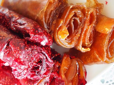 Fruit pastille background. Berry roll-ups made from raspberry, currant, apples, apricots close up