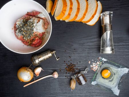 minced meat, meat patties, rissole Ingredients: raw minced meat , raw egg, chopped onion,garlic, bread, herbs, salt and pepper on wooden background