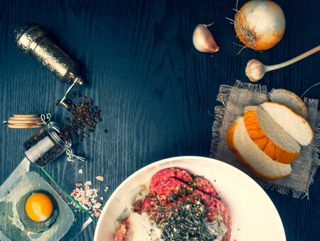 Preparing meatball with ingredients, such as egg, meat, bread, onion, garlic, herbs on wooden board, copy space, top view Stock Photo