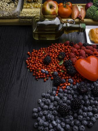 Selection of food that is good for the heart, rustic wood background, heart shape from berry