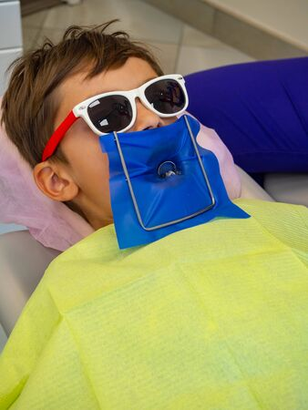 A little boy in dentistry office, Child treated teeth in the dental clinic Stock Photo - 129436985
