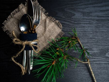 Christmas table cutlery setting in silver tone on wooden table with Christmas branch