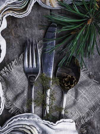 Christmas table place setting. Holidays rustic background, Christmas tree branch, cone