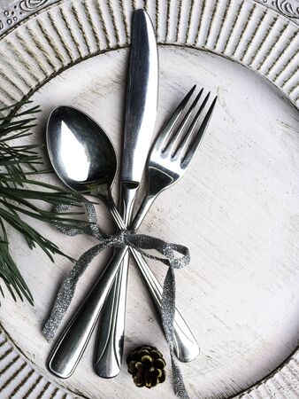 Vintage or rustic christmas table setting Elegant white plate, cutlery and natural pine tree branch on wooden surface