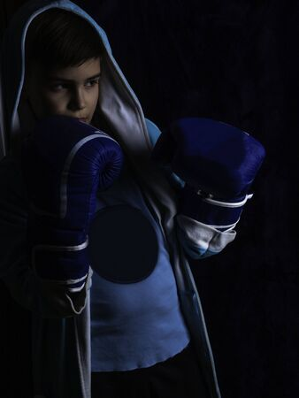 boy in boxing gloves, The defend position portrait on the black background, low key lighting