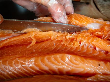 Closeup of workers hands cutting fish with knife at table, selective focus