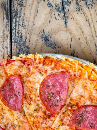 sliced whole salami pizza on a rustic wooden table Stockfoto