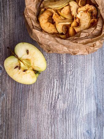 Tasty apple chips in paper bag on wooden table 免版税图像