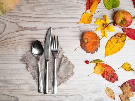 autumn themed place setting with a knife, spoon and fork, burlap napkin, colorful leaves, thansgiving cutlery, copy space for text