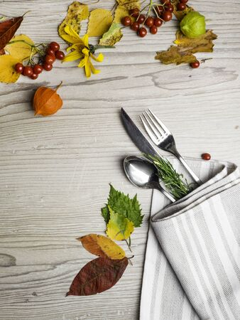 Fall or autumn themed place setting with a knife, fork and napkin, colorful leaves, berry, holiday concept