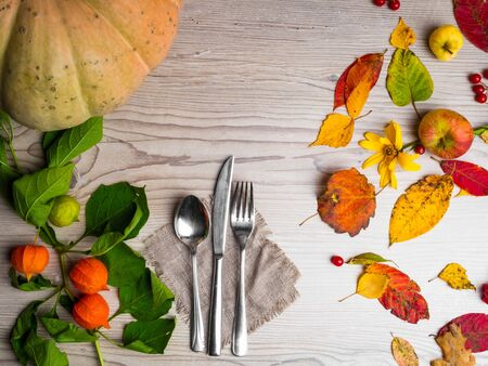 close up of festive thanksgiving autumn cutlery setting and arrangement of colorful fall leaves, red berries
