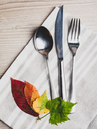 Thanksgiving table setting/ cutlery on the autumn wooden background with autumn leaves, holidays background concept