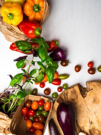 白いテーブルの上にエコ紙袋に生野菜.新鮮なトマト、バジル、ナス、ピーマンのビュー。健康的な食事の概念。フラットレイ、コピースペース 写真素材