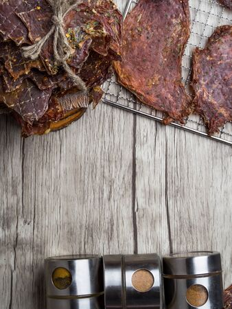 Dried or dehydrated meat slices with spices in jars, copy space Stock Photo