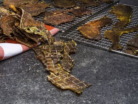 Dried meat slices on metal tray, close up Stock Photo