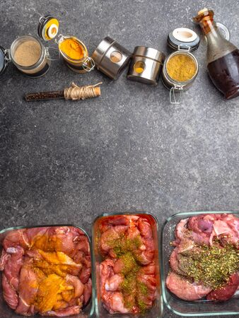 Marinating raw meat in different spices, herbs and marinades, with soy sauce and oil on grey concrete background