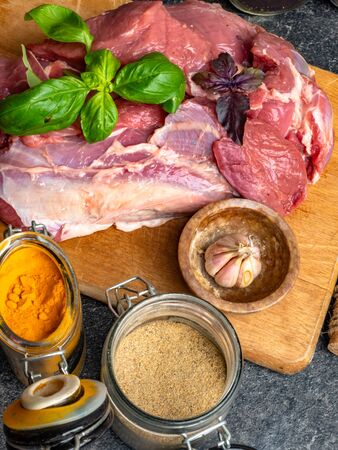 Raw meat with spices in glass jars, fresh basil on a cutting board