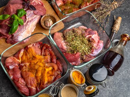 Raw meat background. with a variety of herbs and spices as basil,curcuma, cardamon, pepper on the grey concrete table. Stock Photo